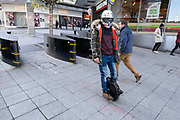 Man wearing a chorome finish crash helmet passes on his self-balanced e-scooter on 26th November 2020 in Birmingham, United Kingdom. An electric unicycle or EUC, is a self-balancing personal transporter with a single wheel. The rider controls speed by leaning forwards or backwards, and steers by leaning and twisting the unit side to side with their feet. The self-balancing mechanism uses gyroscopes and accelerometers.