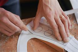 Model maker at work carving pattern onto model,