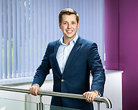 Corporate portrait shot to half body features young businessman holding railings in reception area with windows blinds behind