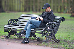 © Licensed to London News Pictures 15/01/2021.         Greenwich, UK. A man rolling his own cigarette while sitting on a bench in Greenwich park, London during a third national Coronavirus lockdown. Photo credit:Grant Falvey/LNP
