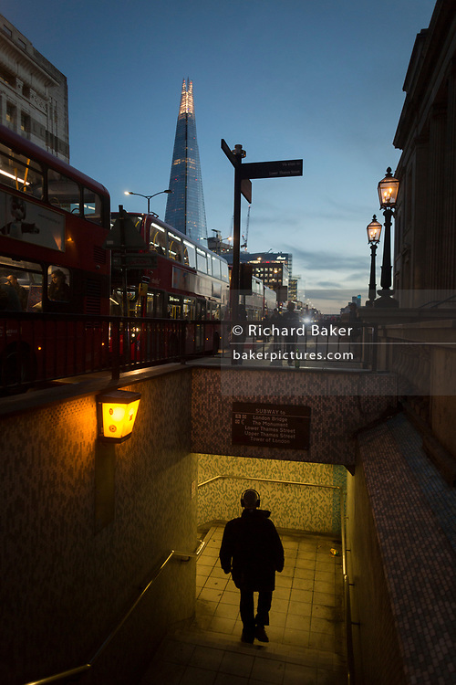 With the Shard in the background, a male pedestrian descends the steps into the tunnel under London Bridge during the evening rush-hour, on 8th November 2018, in London, England.