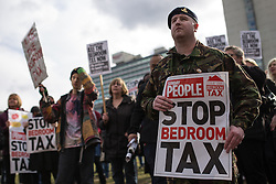 © Licensed to London News Pictures . 16/03/2013 . Manchester , UK . Former Gunner Cody Lachey (right, in fatigues) , who says he'll be made homeless by the new law . Protesters opposed to changes to housing benefit , known as the Bedroom Tax , hold an impromptu (unsanctioned) march through Manchester City Centre today (16th March) . The government plans to introduce changes to housing benefit from this April which will see some claimants receive a reduced amount if they have excess living space . Photo credit : Joel Goodman/LNP