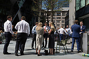 Lunchtime City workers enjoy drinks in summer sunshine outside the Swiss Re building aka The Gherkin, in the City of London, the capitals financial district aka the Square Mile, on 22nd August 2019, in London, England.