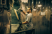Tommy Hardison sprays bats down with a clear gloss finish at the Louisville Slugger factory.