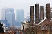 A view of the towers of the old Electric Power Station in Greenwich across the Thames to the towers of Canary Wharf