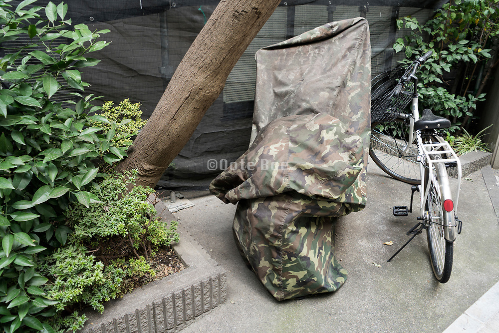 camouflaged covering of a motorcycle in urban garden setting with bicycle