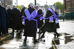© Licensed to London News Pictures. 01/10/2019. London, UK. A Circuit Judge leaps over a puddle of rainwater as the Judges leave Westminster Abbey for The Houses of Parliament after attending the annual service to mark the start of the legal year. The start of the new legal year is marked with a traditional religious service in Westminster Abbey followed by a procession to The Houses of Parliament where the Lord Chancellor (Justice Secretary) hosts a reception.   Photo credit: Dinendra Haria/LNP