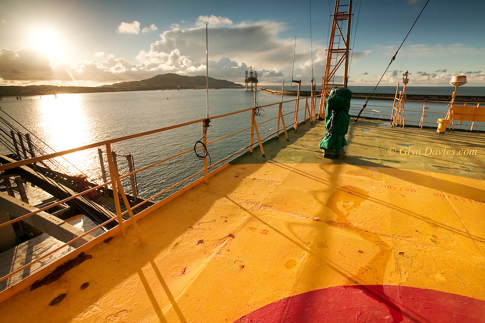 A Malaysian bulk carrier is moored up alongside the Angleey Aluminium Wharf in Holyhead Harbour. This shot was taken from the very top deck above the bridge, looking towards an oil rig in for repairs. The huge breakwater in the background is what makes this such a well protected harbour.