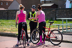 Portobello, Scotland, UK. 8 May 2020. Images from Friday afternoon during Covid-19 lockdown on promenade at Portobello. Promenade and beach were busier than in recent weeks due to warm sunny weather and the fact that several cafes and takeaway food shops are now open. Police patrols were low key. Pictured; Police talk to two female cyclists. Iain Masterton/Alamy Live News