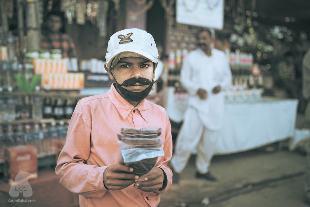 A boy selling fake mustaches and beards, Pushkar, Rajasthan, India.