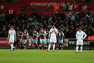 Swansea city players Angel Rangel (l) Mike van der Hoorn © and Leon Britton, the captain (c) stand dejected as they concede another goal. Premier league match, Swansea city v West Ham United at the Liberty Stadium in Swansea, South Wales on Boxing Day, Monday 26th December 2016.<br /> pic by  Andrew Orchard, Andrew Orchard sports photography.