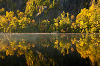 early morning light creates a mirror like reflection on Chapel Pond in High Peaks region of the Adirondacks in New York