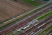 Nederland, Zuid-Holland, Zwijndrecht, 23-10-2013; Kijfhoek, rangeerterrein voor goederentreinen met verdeelsporen. Kijfhoek huisvest Keyrail, exploitant Betuweroute en is in beheer bij ProRail. De Betuweroute, die begint als Havenspoorlijn op de Maasvlakte, verbindt via Kijfhoek de Rotterdamse haven met het achterland. Het rangeeremplacement dient voor het sorteren van goederenwagons waarbij gebruik gemaakt wordt van de zwaartekracht, het 'heuvelen': de wagons worden de heuvel opgeduwd, bij het de heuvel afrollen komen ze, door middel van wissels, op verschillende verdeelsporen. Railremmen zorgen voor het automatisch remmen van de wagons. Na het heuvelproces staan de nieuw samengestelde treinen op aparte opstelsporen.<br /> Kijfhoek, railway yard used by ProRail and Keyrail (Betuweroute operator). Kijfhoek connects via the Betuweroute (beginning as Havenspoorlijn on the Maasvlakte), through the port of Rotterdam with the hinterland. The shunting yard for sorting wagons makes use of gravity. The new trains are assembled on separate tracks.<br /> luchtfoto (toeslag op standard tarieven);<br /> aerial photo (additional fee required);<br /> copyright foto/photo Siebe Swart