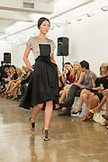 Dress with black pleated dip hem skirt and top with black bib and silver-gray open weave fabric. By Carmen Marc Valvo at the Spring 2013 Fashion Week show in New York.