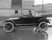 9304-140. A woman wearing stylish white driving gloves in a new 1916 Overland four door auto. Location is in front of the historic United States Customhouse at NW Davis at Broadway, on the NW Corner (camera looking NE) in Portland, Oregon.  All three buildings are still standing. Photo taken winter 1915-16, likely for the Auto show held nearby at the Armory in January 1916.