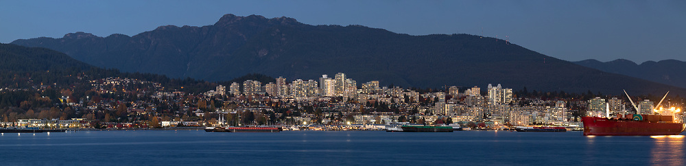 North Vancouver and Mount Seymour above Burrard Inlet in the early evening after sunset.  Burrard Inlet sees many transport ships coming to and from the Port of Vancouver and many are anchored there waiting to offload or load.  Photographed from Brockton Point at Stanley Park in Vancouver, British Columbia, Canada.