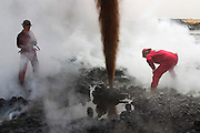 """Boots and Coots team members study a gushing oil well minutes after the fire was extinguished. The ground is still smoking. Well capped two hours later using a """"stinger,"""" a tapered pipe on the end of a long steel boom controlled by a bulldozer. Drilling mud, under high pressure, is pumped through the stinger into the well, stopping the flow of oil and gas. The Rumaila field is one of Iraq's biggest oil fields with five billion barrels in reserve. Rumaila is also spelled Rumeilah."""