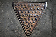 Maintenance Hole- and Drain Covers of Wirral by Colin McPherson, 2020-21.<br /> <br /> A distinctive triangular 'Hartlid' maintenance hole (manhole) cover, dating from 1970 the design of which was patented by Simon-Hartley Limited of Newcastle-under-Lyme, Staffordshire in 1942 and has been in wide use ever since on England's road network.