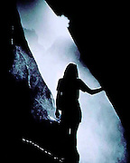 Brochure cover photo of a woman emerging from a cave into the mist of a waterfall in Yosemite National Park, California