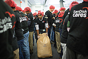 """A SanDisk employee drags a bag of soy in between volunteers during the Stop Hunger Now Foundation's """"Mayday, Mayday"""" food-packing event at SanDisk Corporation in Milpitas, California, on May 13, 2014. (Stan Olszewski/SOSKIphoto)"""