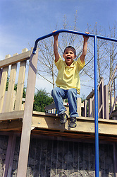 Young boy swinging on metal bar in children's playground,