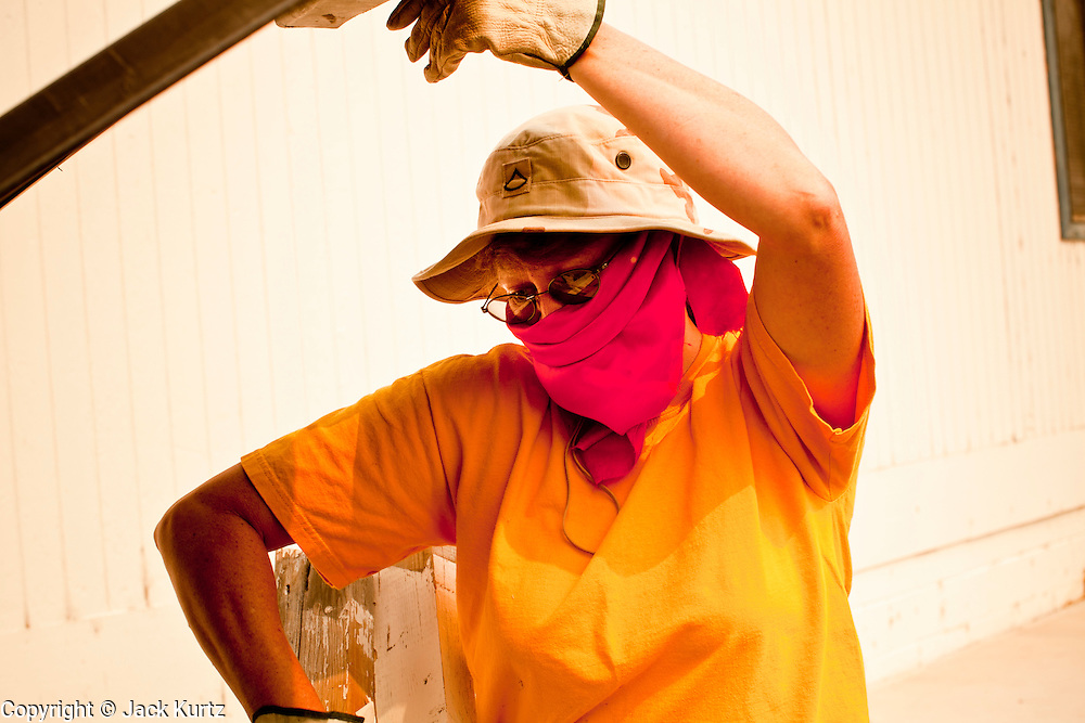 """04 JUNE 2011 - EAGAR, AZ: Mary Elliott (CQ) wore a bandana because of smoke from the Wallow Fire while she cleaned up the land around Life in Christ Fellowship Church in Eagar Saturday. The fire grew to more than 140,000 acres early Saturday with zero containment. A """"Type I"""" incident command team has taken command of the fire.  PHOTO BY JACK KURTZ"""