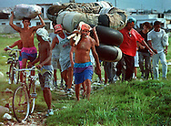 8/19/1994-Al Diaz/Miami Herald--Cubans carry their homemade rafts as they walk along a rocky trail on their way to the shore line of Cojimar, Cuba. In 1994 Cuban balseros turned the tiny fishing village of Cojimar into a major point of embarkation for thousands seeking a better life.