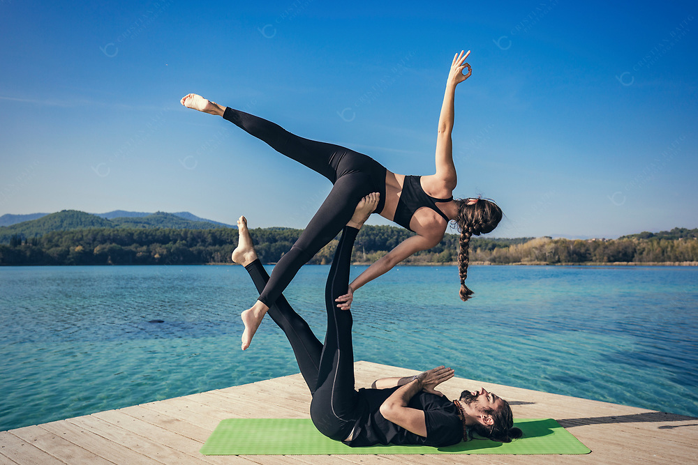 Couple practicing acroyoga in nature at beautiful lake Acroyoga side star pose