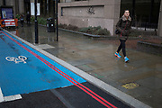 Woman with trainers which match the double red lines and blue Cycle Superhighway. London, England, UK.