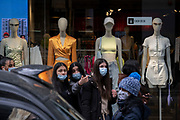 On the day that the UK government eased Covid restrictions to allow non-essential businesses such as shops, pubs, bars, gyms and hairdressers to re-open, young women shoppers look across Oxford Street in front of fashion mannequins, on 12th April 2021, in London, England.