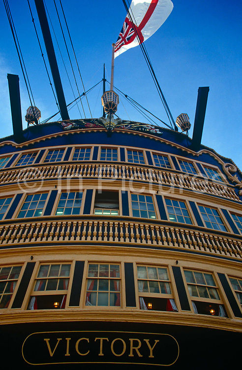 The stern of Admiral Lord Nelson's flagship HMS Victory at Portsmouth. We look up at the rear of Britain's most famous warship from the Napoleonic war era and see the windows of Nelson's cabins and rooms - the location where the battle of Trafalgar was planned and where Nelson died on that day in 1805. Victory took Nelson's body to England where, after lying in state at Greenwich, he was buried in St. Paul's Cathedral on 6 January 1806.<br /> HMS Victory is a 104-gun first-rate ship of the line of the Royal Navy, laid down in 1759 and launched in 1765. After Trafalgar, she served as a harbour ship, moved in 1922  to a dry dock at Portsmouth, England, and preserved as a museum ship. She is the flagship of the First Sea Lord and is the oldest naval ship still in commission