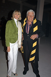 GUNTHER SACHS and his wife MIRJA SACHS at an exhibition of work by Rolf Sachs - a unique world-renowned contemporary furniture designer, held in association with the Louisa Guinness Gallery and held at 250 Brompron Road, London on 6th October 2004.<br />