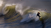 With a high surf building, a surfer rides a wave to take advantage of the conditions at Huntington Beach, CA.
