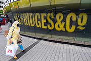 With most shops now open but with retail sales suffering due to the Coronavirus pandemic, upmarket department store Selfridges & Co has announced 450 job losses, as people wearing face masks pass a sign outside their flagship shop at the Bull Ring on 3rd August 2020 in Birmingham, United Kingdom. The department store chain Selfridges is cutting 450 staff after saying that the coronavirus outbreak has led to the toughest year we have experienced in our recent history. Coronavirus or Covid-19 is a respiratory illness that has not previously been seen in humans. While much or Europe has been placed into lockdown, the UK government has put in place more stringent rules as part of their long term strategy, and in particular social distancing.