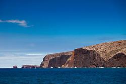 ragged sea cliff and Puu Pehe rock aka Sweetheart Rock in distance, Menele Bay, South Lanai, Lanai aka Pineapple Island because of its past as an island-wide pineapple plantation of Dole, the sixth-largest island of the Hawaiian Islands, Hawaii, USA, Pacific Ocean
