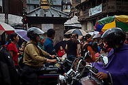 A woman shields herself from the rain as she sells produce in the Thamel district of Kathmandu, Nepal.
