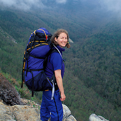 Backpacking. A hiker stands on the ledge with a view of the Franconia Ridge in the fog.  Old Bridle Path Trail, White Mtns, NH
