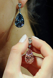 """© Licensed to London News Pictures. 10/04/2017. London, UK. A model presents """"The Apollo Blue"""", a fancy blue vivid diamond weighing 14.54 carats (Est. USD 38-50m) and """"The Artemis Pink"""", a fancy intense pink diamond weighing 16.00 carats (Est. USD 12.5-18m).   The diamonds are the most valuable earrings ever to appear at auction and will be offered for sale by Sotheby's on 16 May in Geneva. Photo credit : Stephen Chung/LNP"""