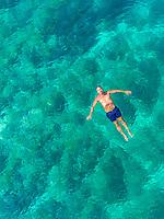Aerial view of man floating in Adriatic sea, Sutivan, Brac island, Croatia.