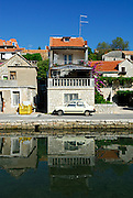 House and reflection in canal,village of Vrboska, island of Hvar, Croatia
