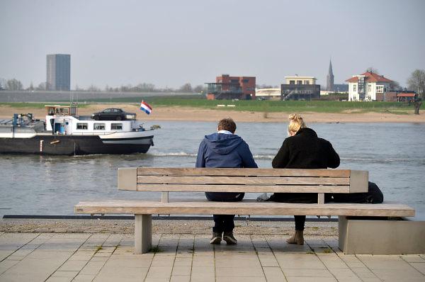 Nederland, Nijmegen, 12-4-2018Een jong stel, vrienden, man en vrouw, zitten op een bankje op de Nijmeegse Waalkade . Eenschip, binnenvaartschip, vaart juist voorbij . Aan de overkant is het eiland veur lent te zien en daarachter links het hotel van van der Valk .Foto: Flip Franssen