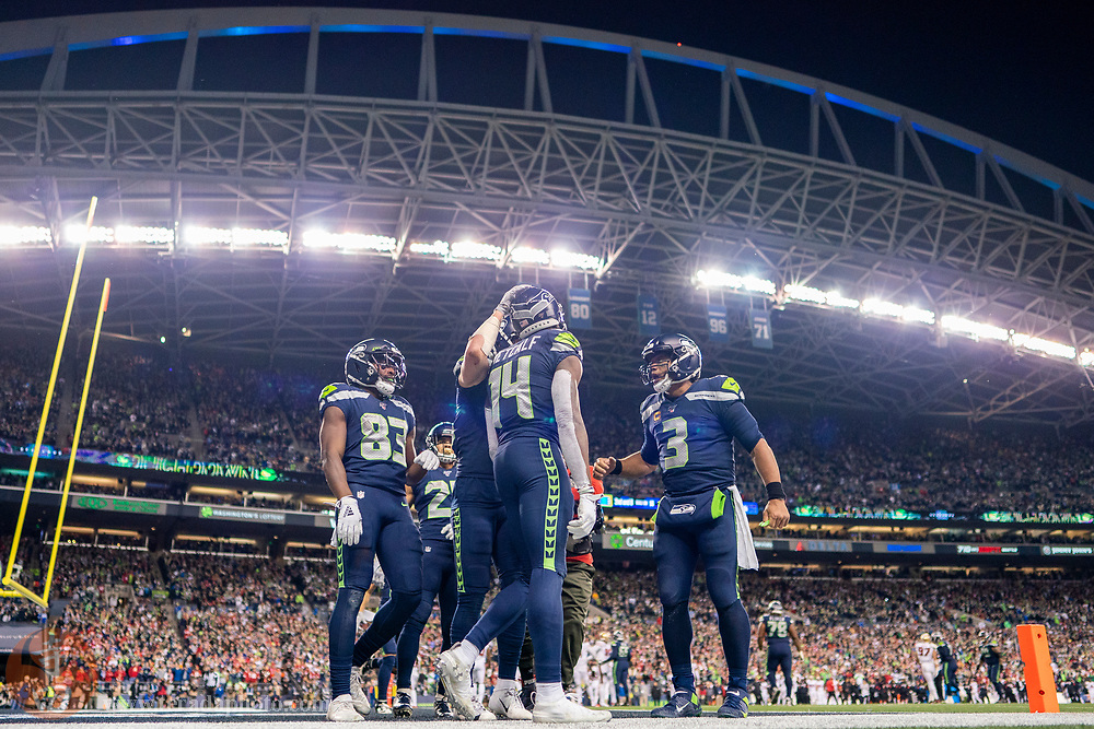December 29, 2019; Seattle, Washington, USA; Seattle Seahawks wide receiver D.K. Metcalf (14) is congratulated by quarterback Russell Wilson (3) for scoring a touchdown during the fourth quarter against the San Francisco 49ers at CenturyLink Field.