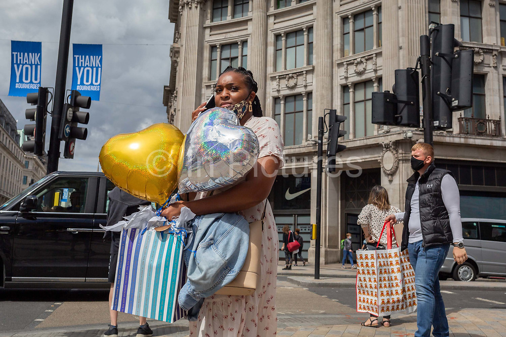 On the day that covid pandemic guidelines for shoppers in England mean that the wearing of face coverings in shops is mandatory, a lady shopper carries party balloons, on 24th July 2020, in London, England.