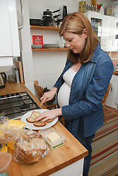 Pregnant woman making a sandwich.
