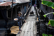 A young girl from a predominantly Muslim village in Chau Doc carries some fresh waffles for a family member's breakfast as her father makes repairs to the wooden walkway. The homes sit on stilts above the shore of the Mekong River, which provides water for the necessities of life. Robert Dodge, a Washington DC photographer and writer, has been working on his Vietnam Unexpected project since 2005. The project has taken him throughout Vietnam, including Hanoi, Ho Chi Minh City (Saigon), Nha Trang, Mue Nie, Phan Thiet, the Mekong, Sapa, Ninh Binh and the Perfume Pagoda. His images capture scenes and people from women in conical hats planting rice along the Red River in the north to men and women working in the floating markets one the Mekong River and its tributaries. Robert's project also captures the traditions of ancient Asia in the rural markets, Buddhist Monasteries and the celebrations around Tet, the Lunar New Year. Also to be found are images of the emerging modern Vietnam, such as young people eating and drinking and embracing the fashions and music of the west. Robert Dodge, a Washington DC photographer and writer, has been working on his Vietnam Unexpected project since 2005. The project has taken him throughout Vietnam, including Hanoi, Ho Chi Minh City (Saigon), Nha Trang, Mue Nie, Phan Thiet, the Mekong, Sapa, Ninh Binh and the Perfume Pagoda. His images capture scenes and people from women in conical hats planting rice along the Red River in the north to men and women working in the floating markets one the Mekong River and its tributaries. Robert's project also captures the traditions of ancient Asia in the rural markets, Buddhist Monasteries and the celebrations around Tet, the Lunar New Year. Also to be found are images of the emerging modern Vietnam, such as young people eating and drinking and embracing the fashions and music of the West.