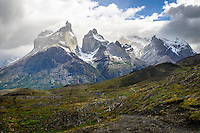 Hikers walk towards the Mirador Cuernos with the Cuernos del Paine and Mont Almirante Nieto towering above them - Torres del Paine, Chile.