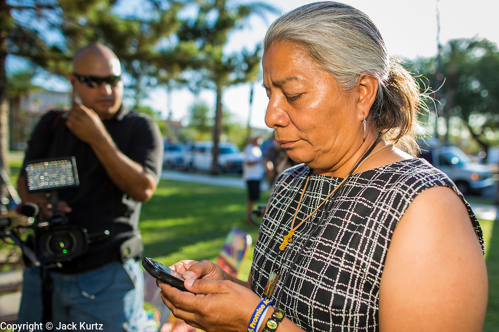 25 JUNE 2012 - PHOENIX, AZ:   PETRA FALCONE, from Promise AZ (PAZ) checks her smart phone to see the US Supreme Court's ruling on SB1070 at the Arizona State Capitol in Phoenix, AZ, Monday. The lawsuit, US v. Arizona, determines whether or not Arizona's tough anti-immigration law, popularly known as SB1070 is constitutional. Among other things, the law requires police officers to check the immigration status of anyone whom they arrest, allows police to stop and arrest anyone whom they believe to be an illegal immigrant, makes it a crime for someone to be in the state without valid immigration papers, and makes it a crime to apply for or hold a job in Arizona without proper papers. The federal government sued Arizona because it believes the law is invalid because it is trumped by federal immigration laws. The court struck down most of the law but left one section standing, the section authorizing local police agencies to check the immigration status of people they come into contact with. PHOTO BY JACK KURTZ