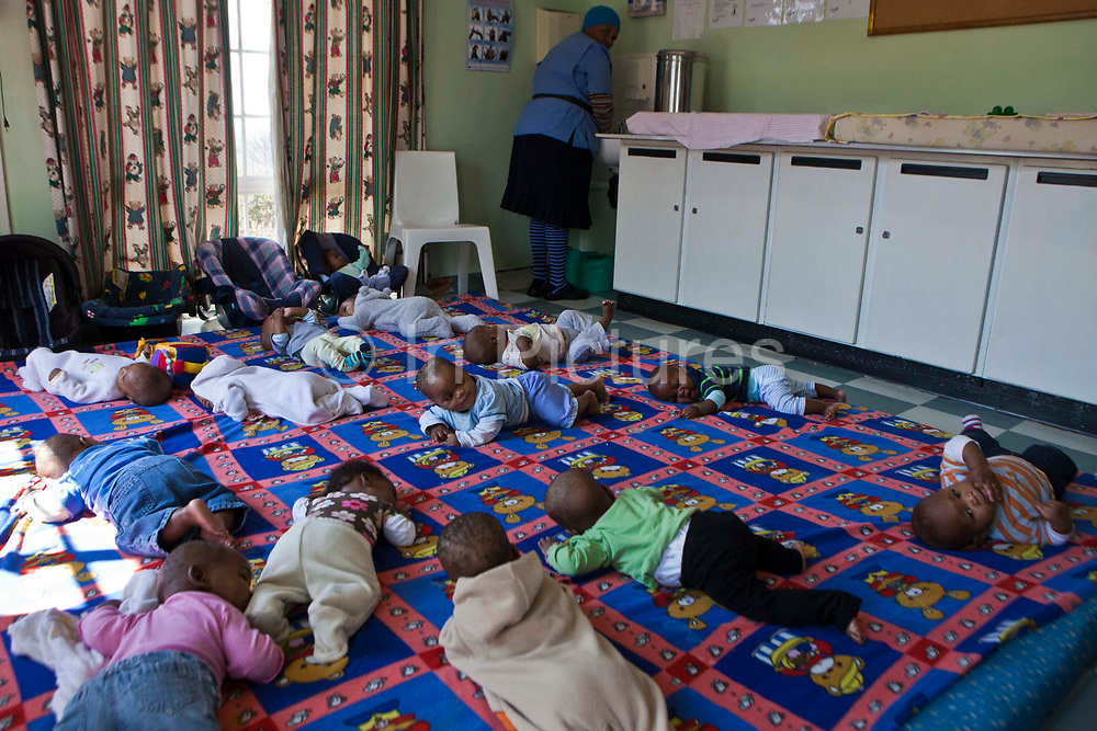 Many babies lying and playing on a large mattress on the floor while their carer washes her hands at Princess Alice's Adoption Home, Guateng, South Africa. Princess Alice's is a children's home in association with BigShoes Foundation. These babies are waiting to be adopted.