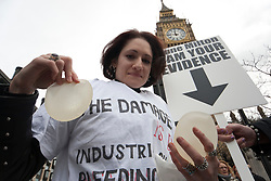 © licensed to London News Pictures. London, UK 18/02/2012. Fiona Harris shows her faulty PIP implants which were removed from her but left industrial silicone inside her body. A group of women who have been affected by faulty PIP implants protesting in Westminster today, 18 February 2012, against NHS and the British Government for the replacement charges and lack of health & safety precautions. Photo credit: Tolga Akmen/LNP