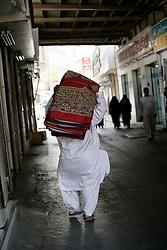 A man carries prayer mats close to the spice souk, Deira, Dubai, UAE, May 9, 2005. Photo by Silvia Baron / i-Images.